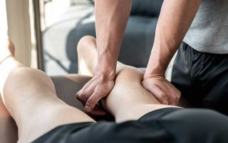 chiropractor performing soft tissue therapy on a persons calf