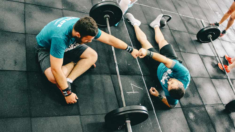 two crossfit athletes stretching after a WOD