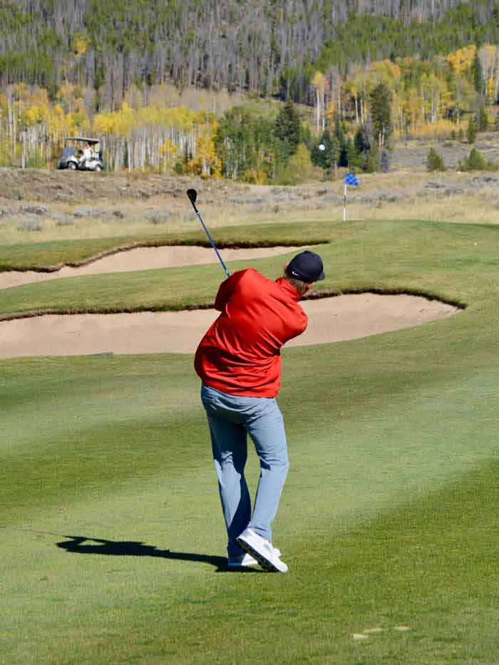 Golfer in a red shirt playing an approach shot to the tee