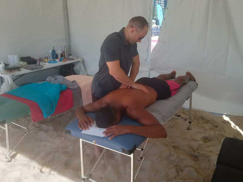 sports chiropractor treating a beach volleyball player